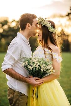 Jonge gelukkig jonggehuwden knuffelen in een park van de lente bij zonsondergang