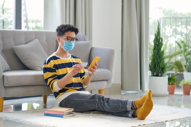 Jonge gelukkig knappe man met medisch masker zittend op de vloer kopen online tikken op smartphone.