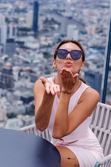 Jonge gelukkig lachend blanke vrouw reiziger in passende jurk en zonnebril op hoge verdieping in bangkok stijlvolle vrouw verkennen geweldig uitzicht op de grote stad