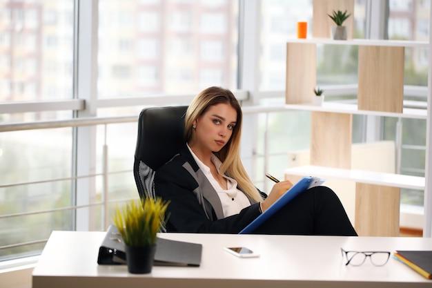 Jonge gelukkig lachend zakenvrouw werken op kantoor