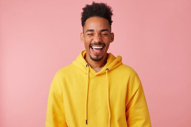 Jonge gelukkig lachende afro-amerikaanse man in gele hoodie, hoorde een heel grappige grap en lachte