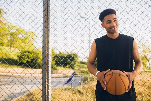 Jonge gelukkig lachende man aan het sporten, basketbal spelen bij zonsopgang