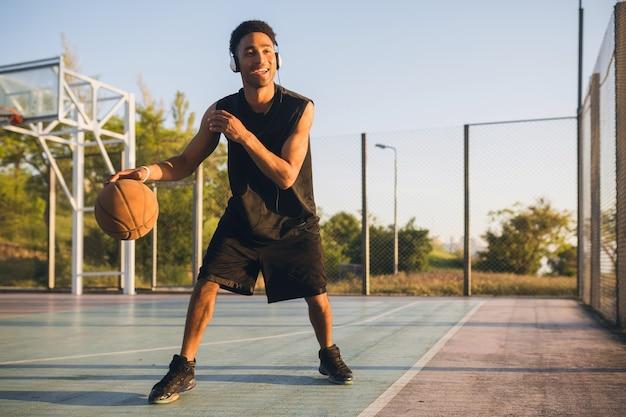 Jonge gelukkig lachende man die sport doet, basketbal speelt bij zonsopgang, naar muziek luistert op een koptelefoon