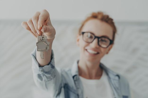 Jonge gelukkig lachende roodharige vrouw in vrijetijdskleding met huissleutels van haar nieuwe huis thuis