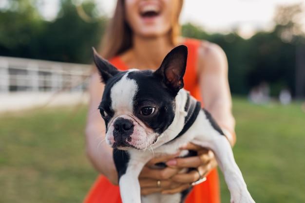 Jonge gelukkig lachende vrouw in oranje jurk plezier spelen met hond in park, zomer stijl, vrolijke sfeer