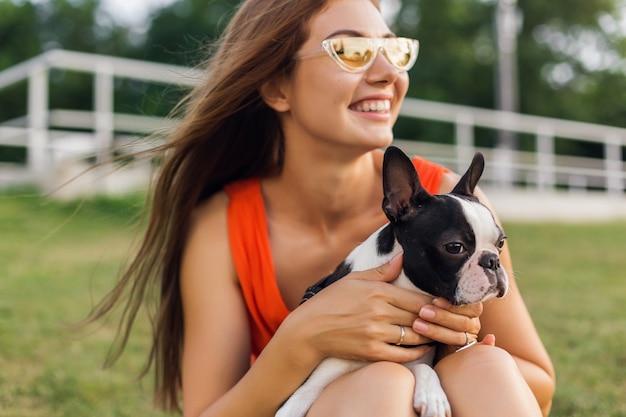Jonge gelukkig lachende vrouw in oranje jurk plezier spelen met hond in park, zomerstijl, vrolijke sfeer