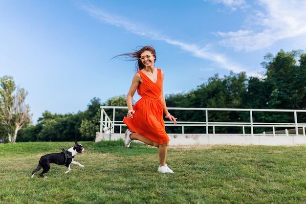 Jonge gelukkig lachende vrouw in oranje jurk plezier spelen met hond in park, zomerstijl, vrolijke stemming