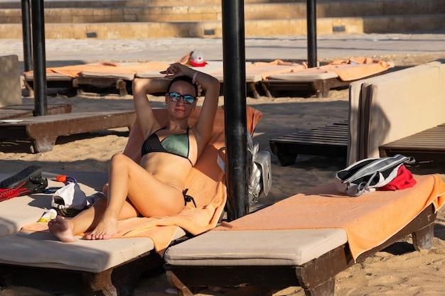 Jonge gelukkig lachende vrouw in zonnebril ontspant op een ligstoel op het strand onder een paraplu