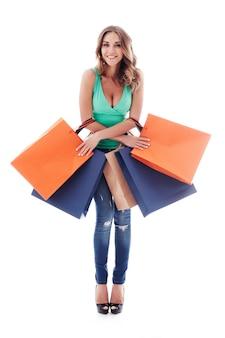 Jonge gelukkig lachende vrouw met boodschappentassen geïsoleerd op een witte achtergrond