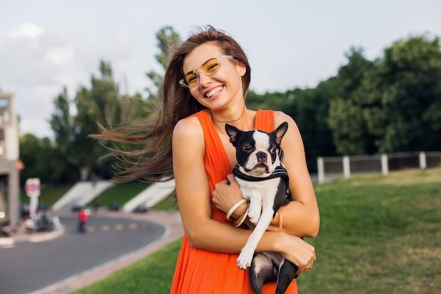 Jonge gelukkig lachende vrouw met boston terriër hond in park, zonnige zomerdag, vrolijke stemming, spelen met huisdier, knuffels, oranje jurk, zonnebril, zomerstijl dragen