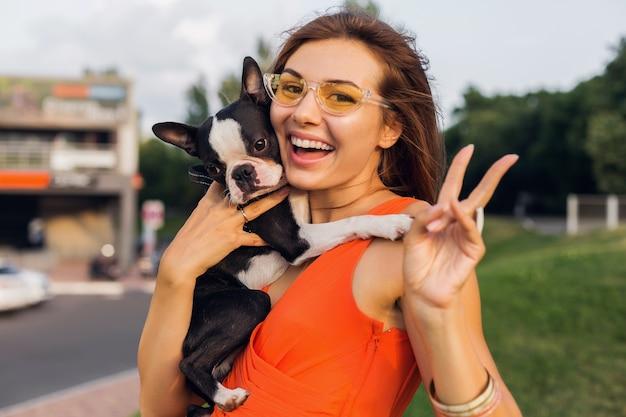 Jonge gelukkig lachende vrouw met boston terrrier hond in park, zonnige zomerdag, vrolijke stemming, spelen met huisdier, lang haar zwaaien, plezier maken, zomer modetrend