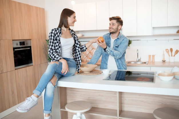 Jonge gelukkig man en vrouw in keuken, ontbijt, paar plezier samen in de ochtend, glimlachen, appel houden