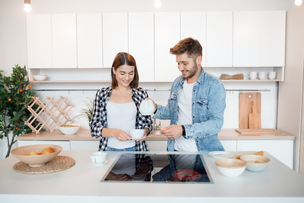 Jonge gelukkig man en vrouw in keuken, ontbijt, paar samen in de ochtend, glimlachen, met thee