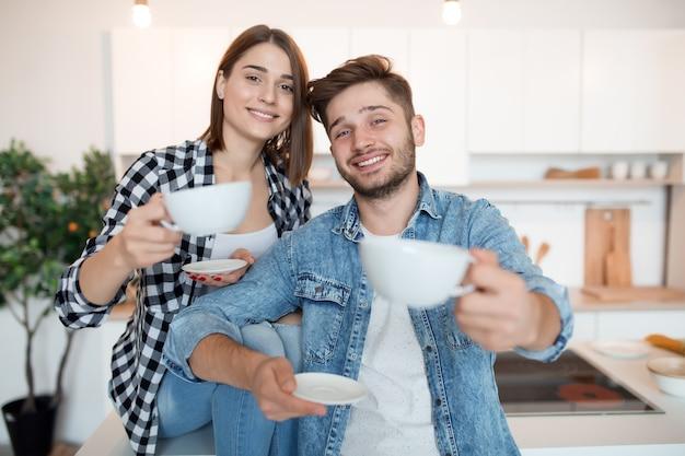 Jonge gelukkig man en vrouw in keuken, ontbijt, paar samen in de ochtend, glimlachend, met thee