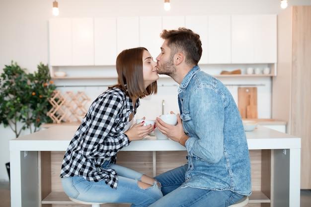 Jonge gelukkig man en vrouw kussen in de keuken, ontbijt, paar samen in de ochtend, glimlachen, thee hebben, kussen, liefde