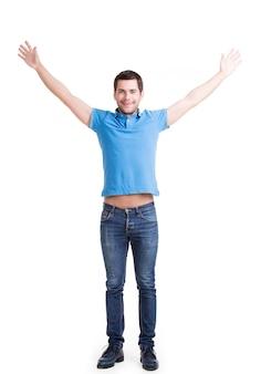 Jonge gelukkig man in casuals met opgeheven handen omhoog geïsoleerd op een witte muur.