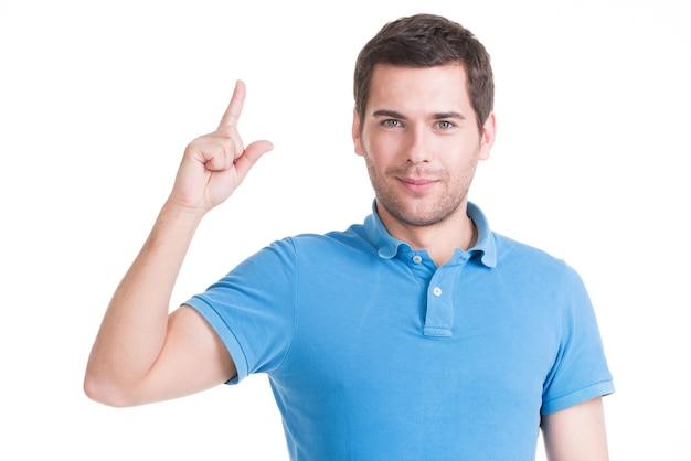 Jonge gelukkig man met een goed idee teken in casuals geïsoleerd op een witte muur.