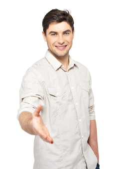 Jonge gelukkig man met handdruk gebaar in casuals geïsoleerd op een witte muur.