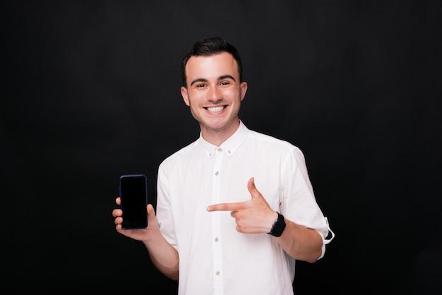 Jonge gelukkig man wijzend op het scherm van zijn smartphone op zwarte achtergrond.