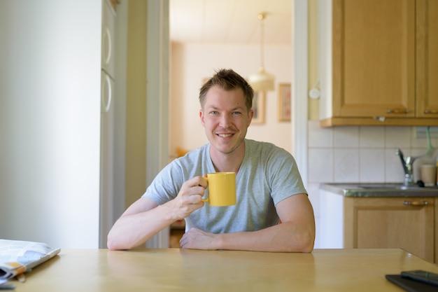 Jonge gelukkig man zitten en koffie drinken bij het raam
