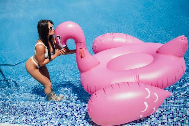 Jonge gelukkig mooie brunette meisje met een mooi figuur houdt in de handen van een opblaasbare flamingo in het zwembad.