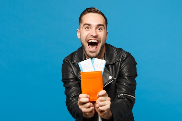 Jonge gelukkig ongeschoren man in zwarte jas wit t-shirt in de hand houden paspoort tickets geïsoleerd op blauwe muur achtergrond. passagier die naar het buitenland reist. lucht vlucht reis concept mock up kopie ruimte