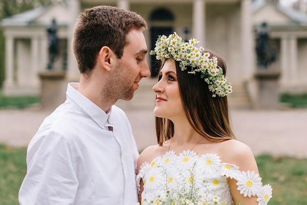 Jonge gelukkig pasgetrouwden knuffelen in een voorjaar park, close-up