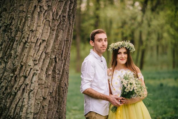Jonge gelukkig pasgetrouwden knuffelen in een voorjaar park