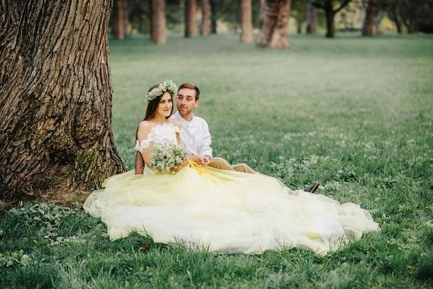 Jonge gelukkig pasgetrouwden zittend op het gras in de buurt van boom in park