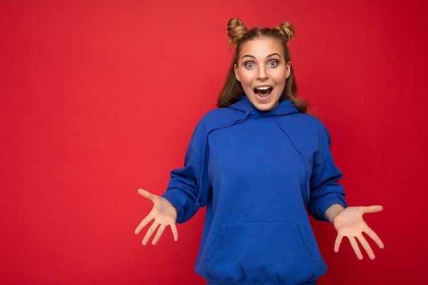 Jonge gelukkig positieve aantrekkelijke emotionele vrolijke blonde vrouw met twee hoorns met oprechte emoties dragen stijlvolle helder blauwe hoodie geïsoleerd op rode achtergrond met kopie ruimte.