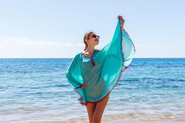 Jonge gelukkig slanke mooie vrouw op het strand, speels, dansen, rennen en plezier hebben in de zomervakantie