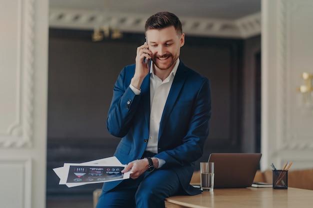Jonge gelukkig succesvolle zakenman in formele kleding praten op mobiele telefoon met partner zittend op het bureau met laptop op kantoor, projectdocumenten vasthouden en zakelijke ideeën bespreken