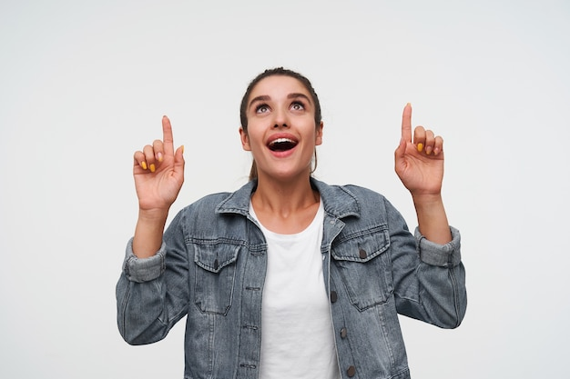 Jonge gelukkig verbaasd brunette dame draagt in wit t-shirt en spijkerjassen, kijkt omhoog en glimlacht in het algemeen, wijst vingers omhoog op kopie ruimte, staat op witte achtergrond.