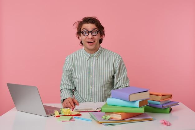 Jonge gelukkig verbaasde man met bril, draagt op een leeg shirt, zit aan een tafel met boeken, werkt op een laptop, kijkt verbaasd, hoort cool nieuws. geïsoleerd op roze achtergrond.