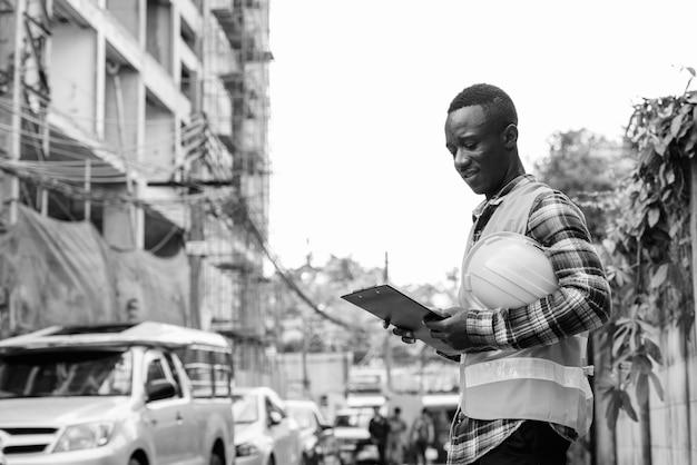 Jonge gelukkig zwarte afrikaanse man bouwvakker lachend tijdens het lezen op het klembord en het houden van harde hoed op de bouwplaats