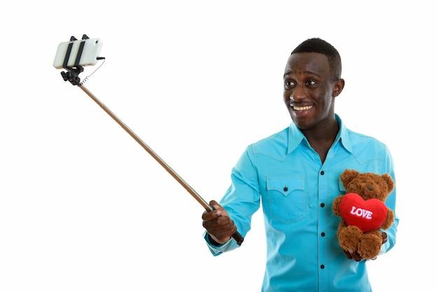 Jonge gelukkig zwarte afrikaanse man glimlachend en teddy beer te houden
