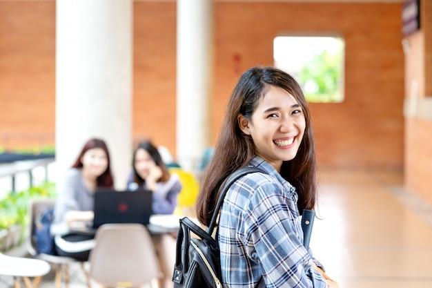 Jonge gelukkige aantrekkelijke aziatische student die aan camera glimlacht