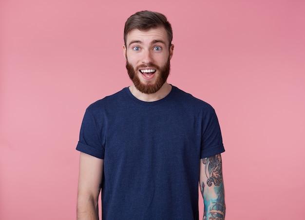 Jonge gelukkige aantrekkelijke jonge kerel met rode baard, gekleed in een blauw t-shirt, kijkend naar de camera met wijd open mond en ogen van verbazing, zag iets leuks, geïsoleerd op een roze achtergrond.