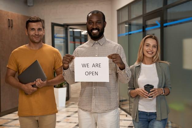 Jonge, gelukkige afrikaanse kantoormedewerker die papier met tekst laat zien, we staan open voor de camera en glimlachen terwijl