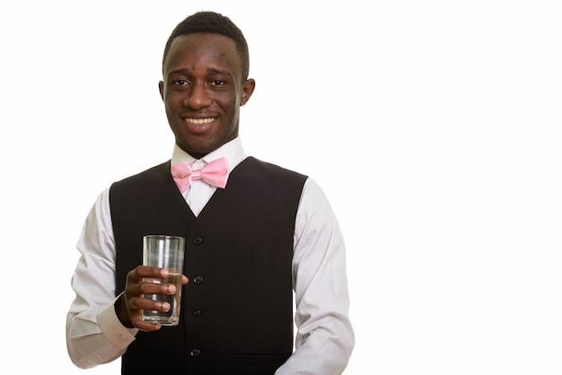 Jonge gelukkige afrikaanse ober die en glas water glimlacht houdt