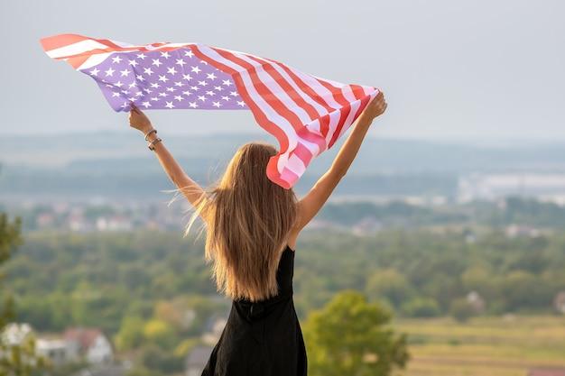Jonge gelukkige amerikaanse vrouw met lang haar die omhoog zwaaiend op de nationale vlag van de wind van de v.s.