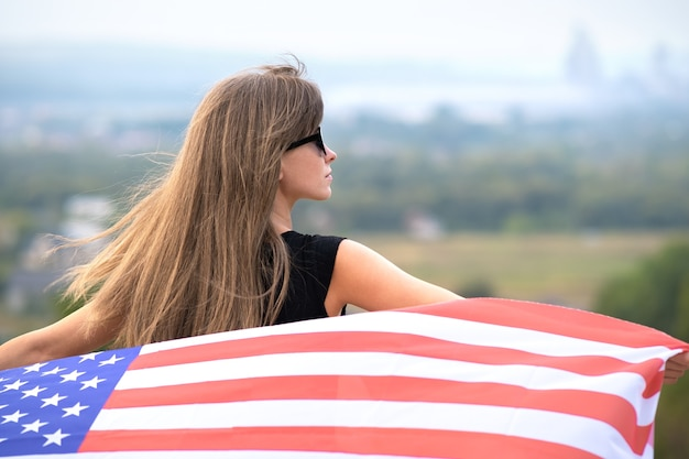 Jonge gelukkige amerikaanse vrouw met lang haar met zwaaien op de wind usa nationale vlag op haar schouders ontspannen buiten genieten van warme zomerdag.