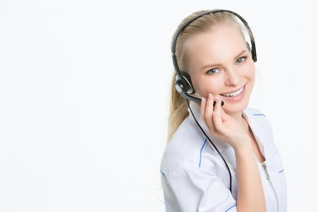 Jonge gelukkige arts in hoofdtelefoon, op kantoor, call centre glimlachende exploitant
