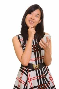 Jonge gelukkige aziatische onderneemster die mobiele telefoon houdt terwijl het denken
