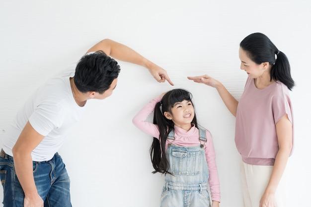 Jonge gelukkige aziatische ouders spelen met hun dochter op studio