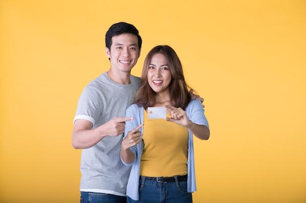Jonge gelukkige aziatische paarvingers die op creditcard richten die op gele muur wordt geïsoleerd