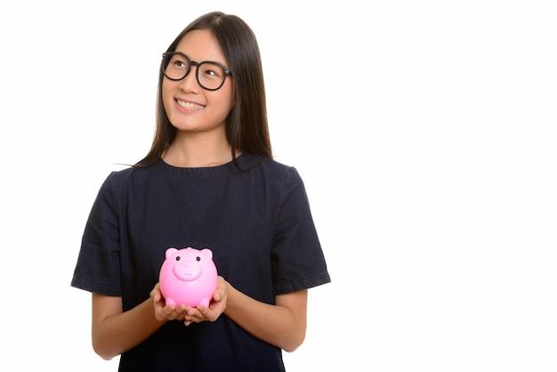 Jonge gelukkige aziatische tiener die en spaarvarken glimlacht houdt