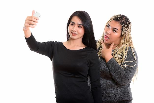 Jonge gelukkige aziatische transgender vrouw en aziatische vrouw lachend