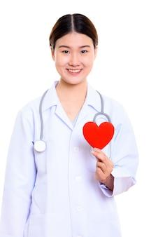 Jonge gelukkige aziatische vrouw arts glimlachen terwijl rood hart geïsoleerd