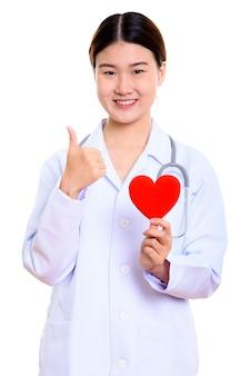 Jonge gelukkige aziatische vrouw arts glimlachen terwijl rood hart vasthouden en duim opgevend